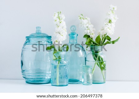 Vintage home decor, white matthiola flowers in different blue glass bottles vases and antique jars on a shelf by the wall - stock photo