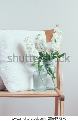 Vintage home decor, white matthiola flowers in different blue glass bottles vases on a chair with pillows by the wall - stock photo