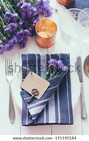 Vintage home table setting with blue napkins, antique cutlery and purple cornflowers on white wooden table. Blank cardboard tag and an old key