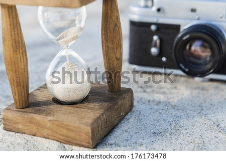 Vintage hourglass and camera in the sand at the beach - stock photo