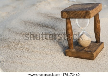 Vintage hourglass in the sand with small shadow - stock photo