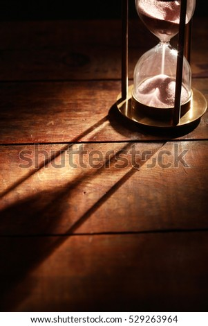 Vintage hourglass on wooden background with long shadow
