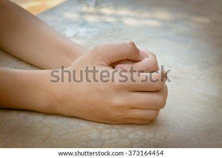 vintage image of child hands folded in prayer at floor - stock photo