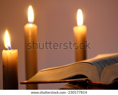vintage image of open book with three candle lights