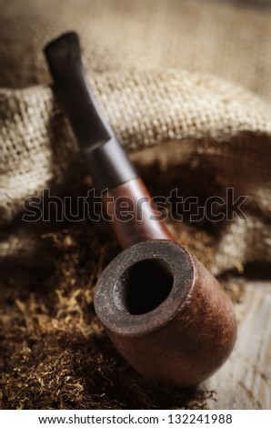 Vintage image of tobacco pipe on wooden background - stock photo