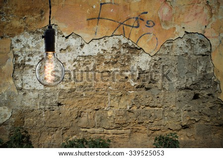 Vintage incandescent bulb on wall background