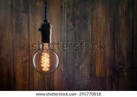 Vintage incandescent Edison type bulb on wooden wall - stock photo