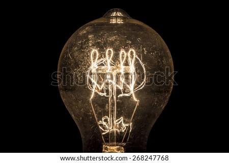 Vintage incandescent light bulb filament on black. - stock photo