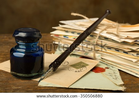 Vintage ink well and fountain pen on a table with old letters - stock photo