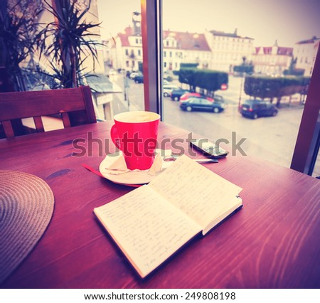 Vintage instagram like toned coffee cup and diary in coffee shop. - stock photo