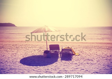 Vintage instagram stylized deckchairs and umbrella at sunset. Concept for holidays and relaxation. - stock photo