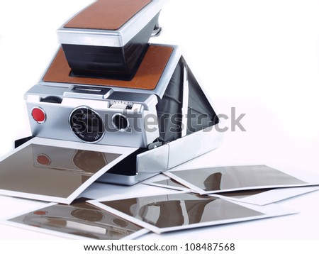 Vintage instant camera with some printed copies.