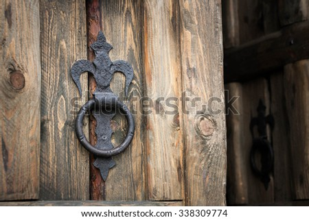 vintage iron handle in the form of a ring on a wooden door - stock photo