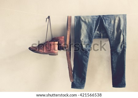 Vintage,Jeans,belt and Leather shoes hanging on the wall - stock photo