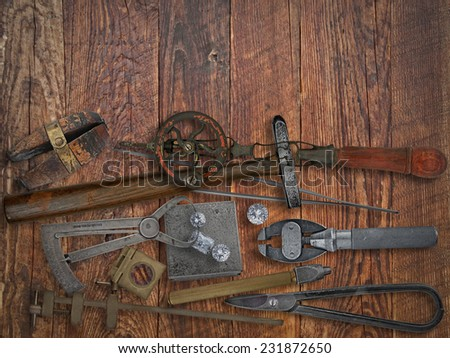 vintage jeweler tools and diamonds over wooden working bench, space for text - stock photo