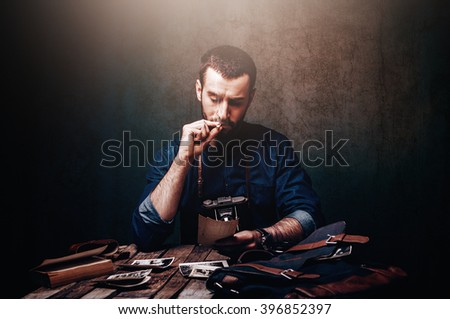 Vintage journalist photographer from the past looking at old archive photographs in historic spy styled darkroom scene