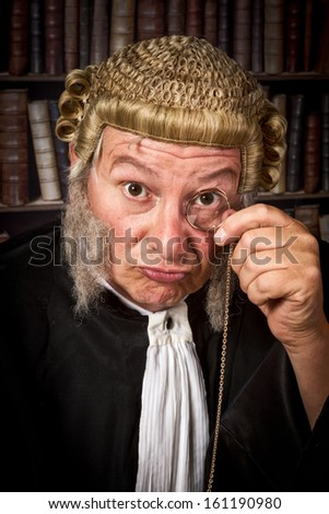 Vintage judge looking through a monocle in court - stock photo