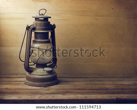 Vintage kerosene lamp on wooden table and wooden background