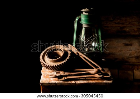 Vintage kerosene lamp with rusty tools and gearwheels on the wooden stool.
