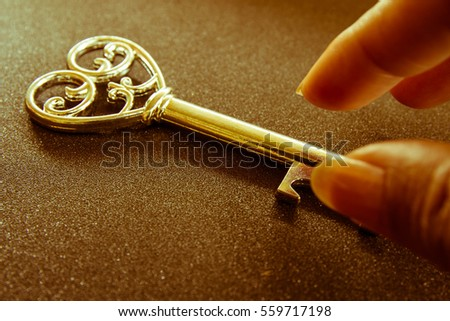 Vintage key and woman hand in dark with light