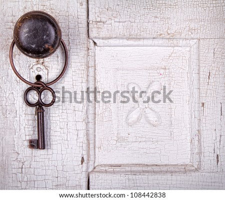 Vintage key hanging on a old cracked antique or vintage door - stock photo