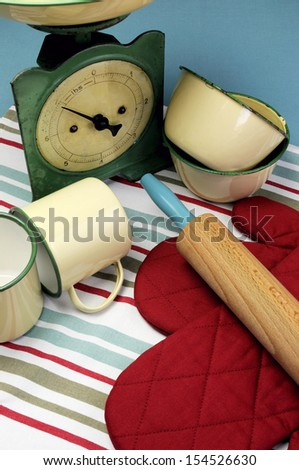 Vintage kitchen equipment including retro scales, yellow and green tin cups and bowls, red oven glove on red, aqua blue and white stripe tea towel. Vertical close up.