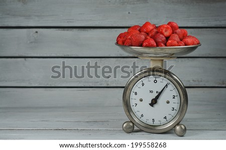 Vintage kitchen scale weighing strawberries on wooden background - stock photo