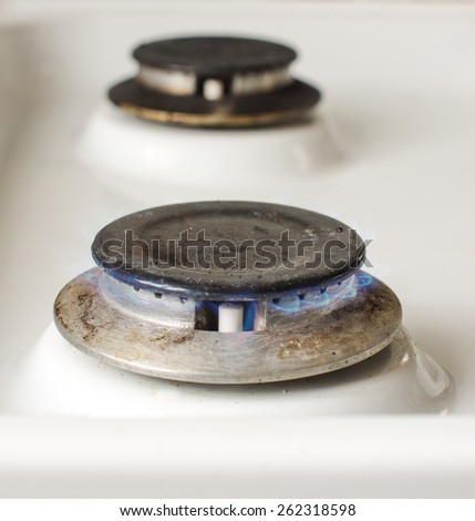 Vintage kitchen stove with blue gas flame close up - stock photo