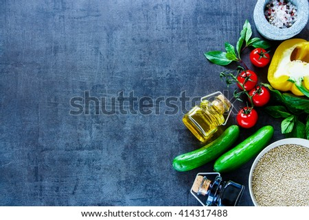 Vintage kitchen table with bowl of healthy white quinoa seeds and fresh colorful vegetables, top view, place for text. Healthy Eating, Diet, Vegetarian or Cooking concept - stock photo