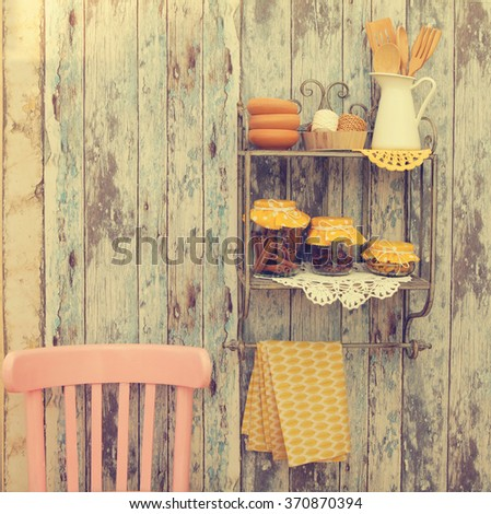 Vintage kitchen utensils and spices(cinnamon,cloves,turmeric) in glass jars on the shelf,rustic chair on a wooden wall