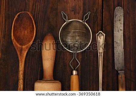 Vintage kitchen utensils on rustic wood background.  Closeup with low key, natural side-lighting for effect. - stock photo