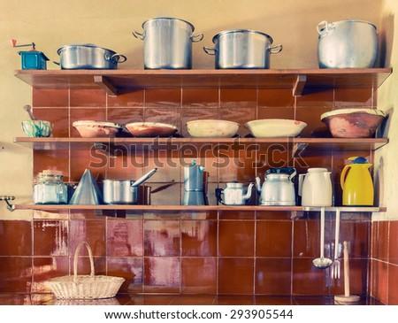 Vintage kitchen utensils on shelves - stock photo