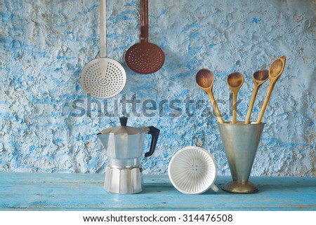 Vintage kitchen utensils; spatulas; espresso maker; skimmer; coffee filter; beaker - stock photo