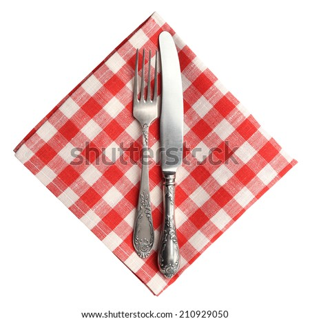Vintage knife and fork on red plaid linen napkin isolated on white background. - stock photo