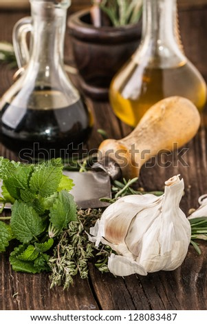 vintage knife with garlic, mint and thyme, oil and vinegar in vintage bottles on old wooden table