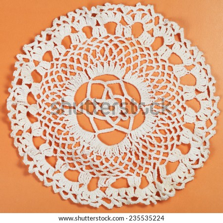 vintage knitting craftsmanship - embroidered crochet lace flower ornament of placemat - stock photo