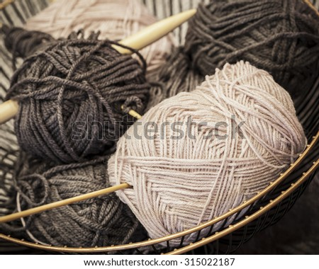 Vintage knitting needles and yarn inside old wire basket, still life photo with soft focus