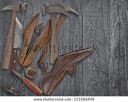 vintage ladies shoe and shoemakers tools over wooden table, space for your text - stock photo