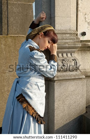 Vintage lady in mourning at an ancient graveyard - stock photo