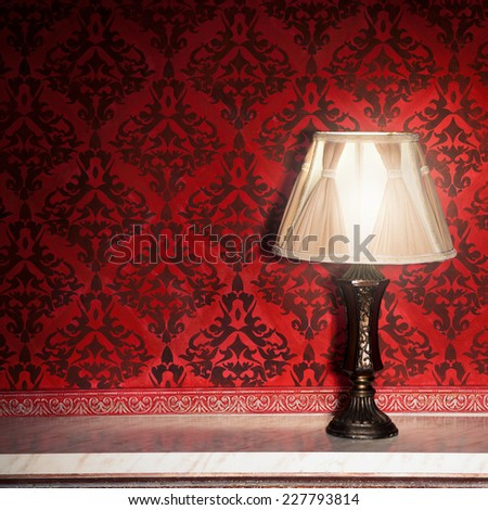 Vintage lamp on old fireplace in room with red rocco pattern. Luxury rocco interior