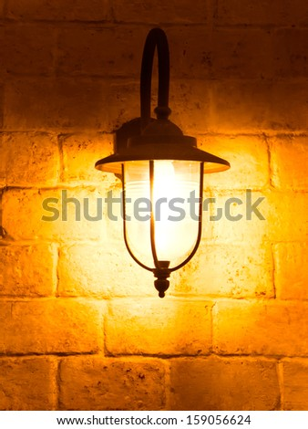 vintage lamp on old wall - stock photo