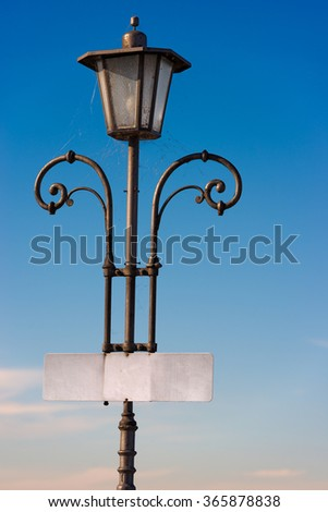 Vintage Lamp Post with Empty Signboard / Old vintage lamp post with blank sign board and cobwebs on a clear blue sky - stock photo