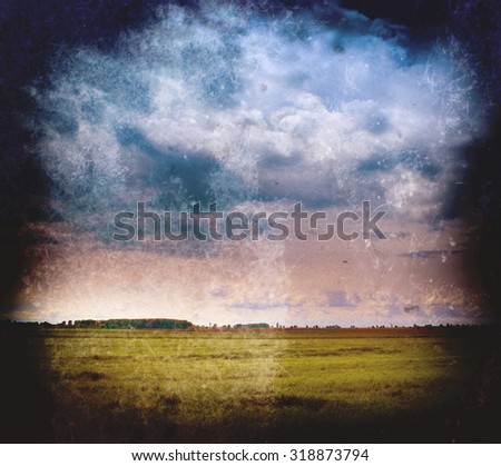 Vintage landscape - cloudy sky and green field - stock photo