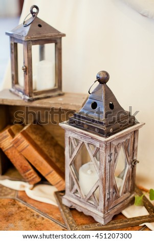vintage lantern with candle and books - stock photo