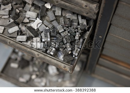Vintage lead letterpress printing blocks against a weathered metal drawer background with bokeh.