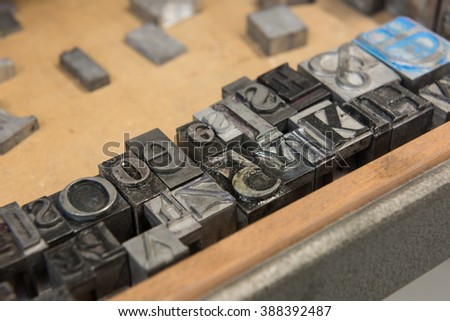 Vintage lead letterpress printing blocks against a weathered wooden drawer background with bokeh.