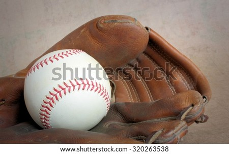Vintage Leather Baseball Glove and Baseball with Red Stitching - stock photo