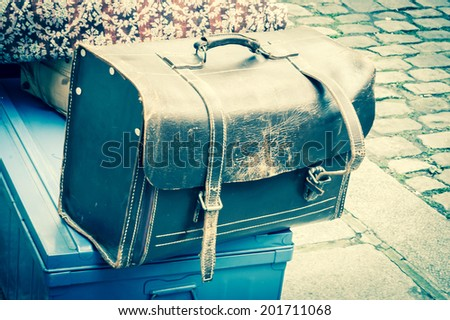Vintage leather briefcase with two straps and brass buckles against pavement background. At flea market in Paris (France). Old times concept. Aged photo. - stock photo