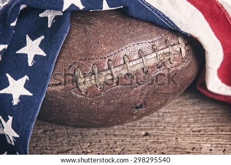 Vintage leather football draped with a vintage American flag on a rustic wooden table with filtered effect