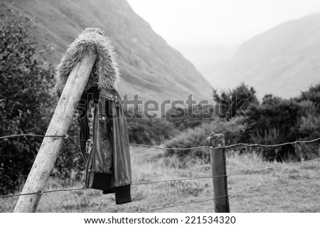 vintage leather jacket left hanging on a fence post - stock photo